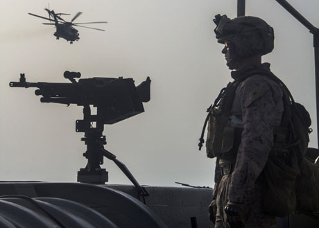 U.S. Marine Corps Lance Cpl. Matthew R. Nesbit, an infantry rifleman assigned to Lima Company, Battalion Landing Team (BLT) 3/2, 26th Marine Expeditionary Unit (MEU), stands guard while a CH-53E Super Stallion helicopter assigned to Marine Medium Tiltrotor Squadron (VMM) 266 (Reinforced), flies over the USS San Antonio (LPD 17), in the U.S. 5th Fleet area of responsibility, June 2, 2013. The 26th MEU, a Marine Air-Ground Task Force, was forward deployed aboard the Kearsarge Amphibious Ready Group serving as a sea-based, expeditionary crisis response force capable of conducting amphibious operations across the full range of military operations. (DoD photo by Lance Cpl. Juanenrique Owings, U.S. Marine Corps)