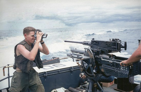 Corporal William T. Perkins Jr., filming U.S. Navy sailors aboard a Patrol Fast Craft, or